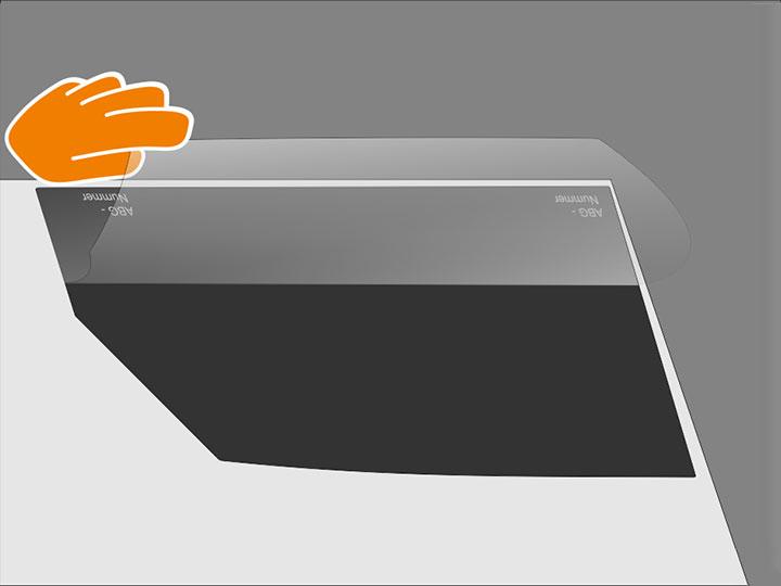 Nimm die Folie vorsichtig von der Außenseite der Scheibe. Zieh nun die Klebeschutzfolie vom oberen Teil der Tönungsfolie ab und schlage diese so auf der Folie um, dass die unteren 5-10 cm der Schutzfolie noch haften bleiben. Vermeide Fingerkontakt mit der trockenen Klebeschicht.