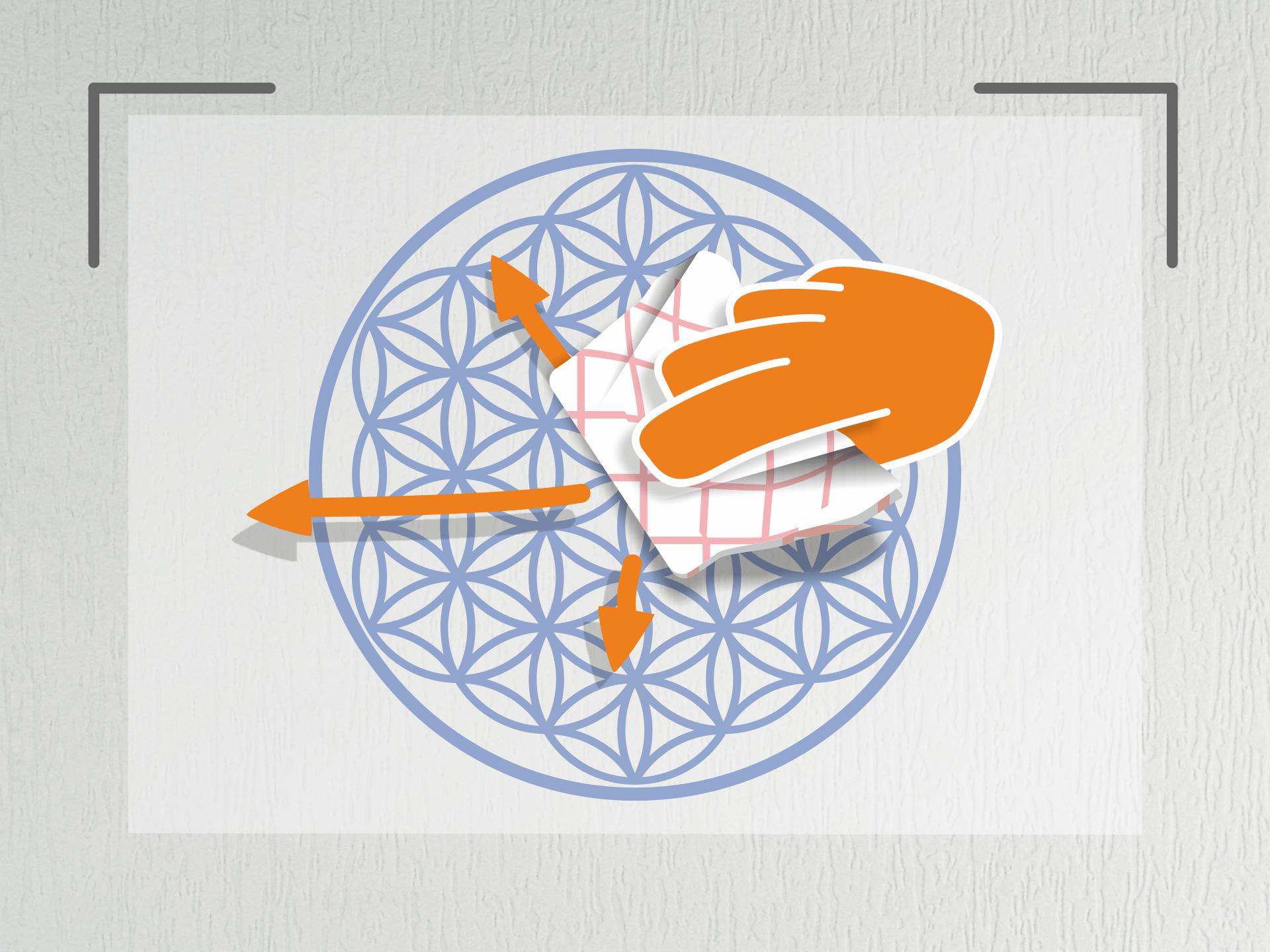 Jetzt den Aufkleber sehr straff halten und an den Markierungen auf der Wand anlegen. Nun das Geschirrtuch zu einem Ballen formen und den Aufkleber (von der Mitte aus) mehrfach andrücken. Bei glatten Wänden kannst Du auch den Rakel zum andrücken nehmen.